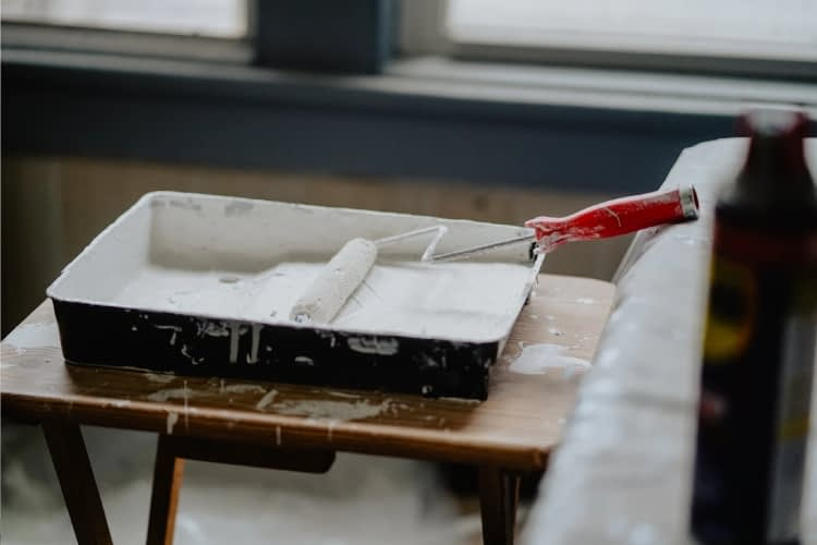A paint roll dipped in white paint is set on a table